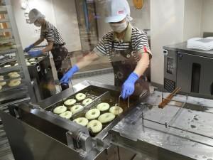 スタッフがドーナツを揚げるところ